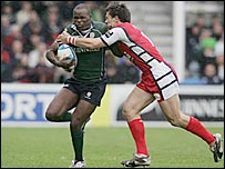 London Irish's Topsy Ojo is tackled by Mark Foster of Gloucester