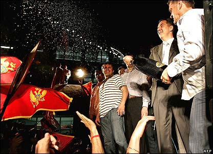 Prime Minister Milo Djukanovic (2nd r) sprays champagne over pro-independence supporters in Podgorica
