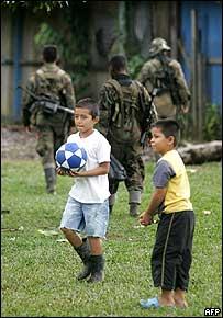 Niños juegan en Putumayo, Colombia, mientas soldados caminan detrás.