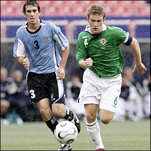 Diego Godin of Uruguay and Northern Ireland's Steve Davis
