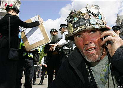 Anti-war protestor Brian Haw speaks on his mobile phone as London police sweep away his ramshackle peace camp in Parliament Square