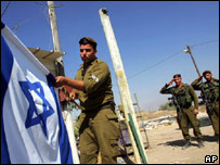 Israeli troops lowering the flag in the Gaza Strip in September 2005