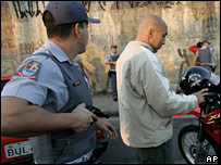 A policeman holds a gun on a suspect at a checkpoint in Sao Paulo on 18 May