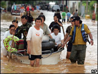 People wade through the streets in Uttaradit province