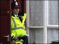 Police officer outside Moss Side address raided