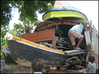 Villagers packing fishing boat onto bus