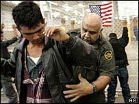 رجل شرطة يفتش احد المهاجرين غير الشرعيين
