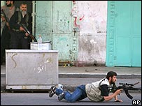 Members of pro-Hamas paramilitary force take cover during gunfight in Gaza