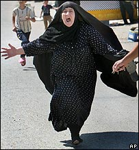 A woman who says she lost three sons in a bomb attack arrives at al-Kindi hospital