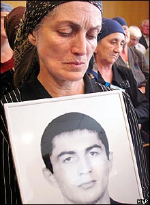A woman holds a picture of her son in the court house on Friday