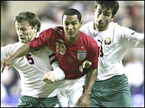 Theo Walcott sandwiched by two Belarus players