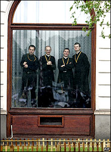 Polish priests watch mass from a window