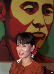 Aung San Suu Kyi sits beneath a portrait of her father General Aung San