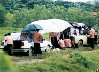 Burma's pro-democracy leader Aung San Suu Kyi (unseen) and her 12 supporters are locked in cars in a roadside standoff in Dala, a small town just outside Yangon, Sunday, Aug. 27, 2000