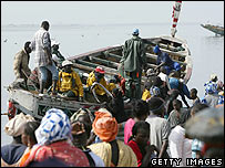 A crowd looks at Senegalese men onboard a boat 23 May 2006 at the fishing port of Get Ndar