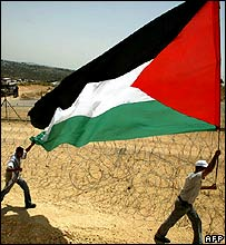 Palestinians carry their flag near the West Bank village of Bilin