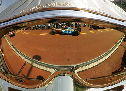 Fernando Alonso's Renault is reflected in a fireman's mask in the Monaco pitlane