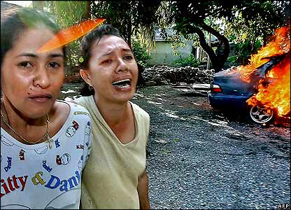 Women pass burning car