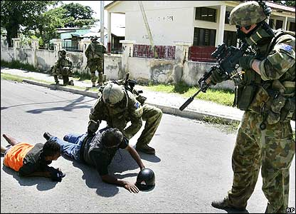 Australian soldiers search men on Dili street