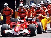 Marshals push Michael Schumacher's Ferrari back to the pits after his controversial late incident in qualifying