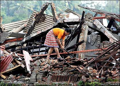 Woman in Yogyakarta searches in wreckage.