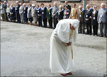 Pope bows in front of the execution wall, watched by Auschwitz survivors