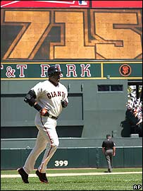 Barry Bonds runs past a scoreboard showing he has beaten Babe Ruth's mark of 714 career home runs