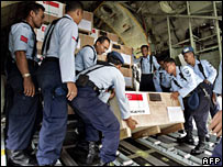 Indonesian soldiers unload medical supplies from Singapore