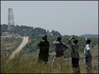 Hezbollah militant and Lebanese civilians watch Israeli warplanes near the border (file picture)