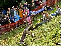 A man in an Australian flag races down Cooper's Hill during the contest