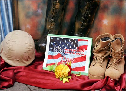 A Memorial Day poster sits between a pair of soldier's boots and a helmet at the US embassy in Baghdad
