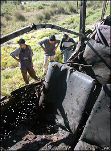 Young Iraqis look at the blackened seats of the bus hit by a bomb in Diyala province