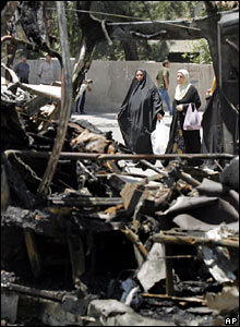 Two Iraqi women look at the wreckage of the minivan in Kazimiya