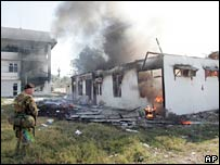 An Australian soldier looks as a building burns in Dili on 30 May 2006