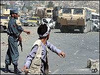 An Afghan protester throws stones at a US military convoy in Kabul