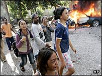 An East Timorese family run past a burning car in Dili