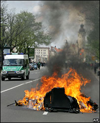 A police van passes bins set alight during a counter demonstration to far-right marches in Leipzig, 1 May 2006