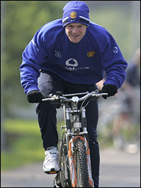 Wayne Rooney rides a bike in training with Manchester United