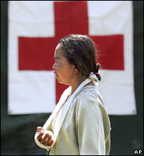 A woman with her arm in a sling stands outside a Singaporean army field hospital  in Bantul