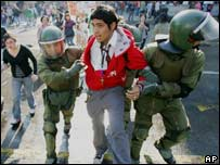 Riot police arrest a student demonstrator in Santiago