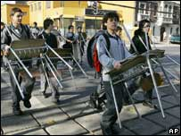 Pupils carry their chairs and desks out of class