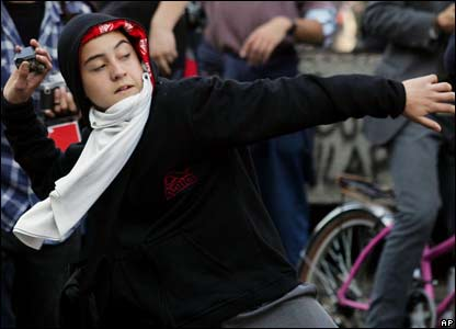 A Chilean student prepares to throw a stone during demonstrations in Santiago