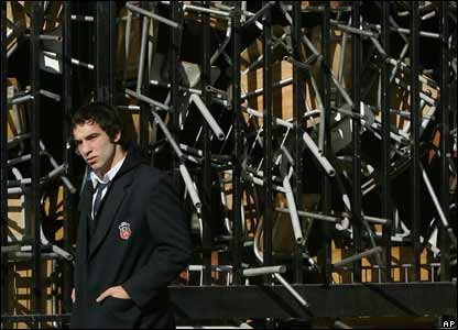 A student walks past the gates of a school in Santiago barricaded by chairs
