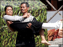 A man carries an injured earthquake victim in Yogyakarta, Indonesia