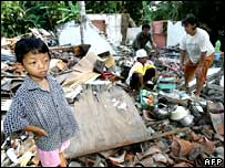 A family gather possessions from the rubble of their home in Yogyakarta, Indonesia