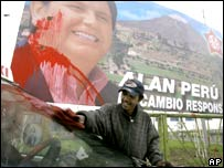 A man cleans a car with an lection poster for  Alan Garcia in the background