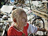 An elderly woman sits in the wreckage of her house, in Bantul district