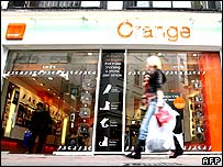 Woman walking past an Orange mobile phone shop