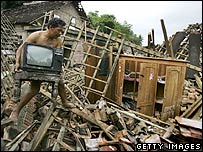 Hassim carries a TV found in the rubble of his destroyed home June 1, 2006 in Bantul, Indonesia.