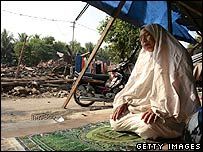Tarmo prays by her destroyed home June 1, 2006 in Bantul, Indonesia.